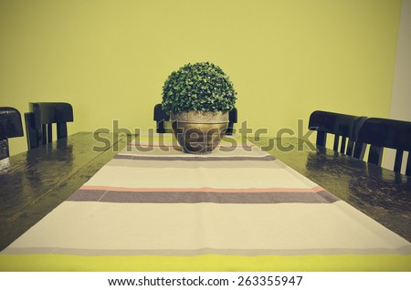 Dining table with vase and table runner - stock photo