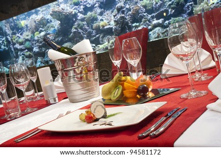 Dinner in good restaurant, serving salmon specialty, fruit and champagne. - stock photo