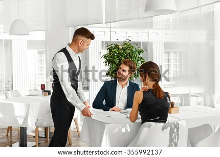 Dinner In Restaurant. Waiter Serving Happy Romantic Young Couple In Love. Cheerful People Making Orders, Celebrating Anniversary Or Valentine's Day. Love, Romance, Relationships Concept.  - stock photo