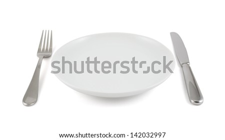 Dinner is served composition: table knife, fork next to the ceramic empty copyspace plate dish isolated over white background - stock photo