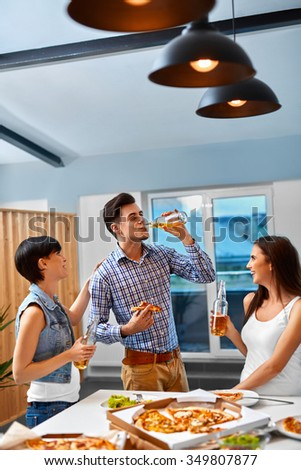 Dinner Party At Home For Friends. Group Of People Having Fun, Eating Pizza, Drinking Beer And Celebrating Holiday Indoors. Friendship, Leisure, Celebration Concept. Fast Food - stock photo