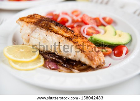 Dinner Plate with Grilled Cod Salad on Side - stock photo