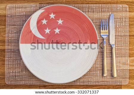 Dinner plate with the flag of Singapore on it for your international food and drink concepts. - stock photo