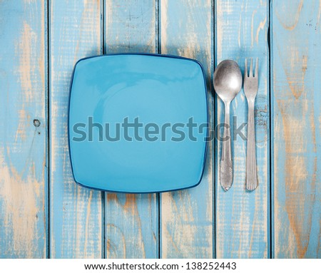 Dinner set on painted blue wooden background - stock photo