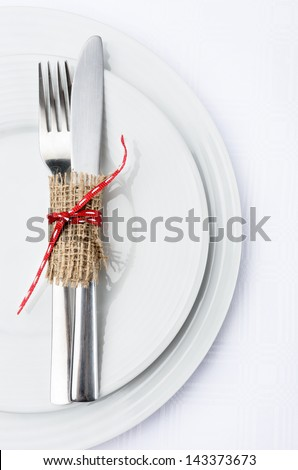 Dinner setting with white plates crockery and silver cutlery tied with hessian and a red ribbon bow, simple rustic elegant table decor - stock photo
