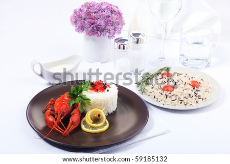 Dinner table dished up with  boiled crawfish, rice and clean water. - stock photo