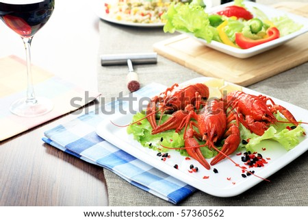 Dinner table dished up with  boiled crawfish, vegetable salad and red wine. - stock photo