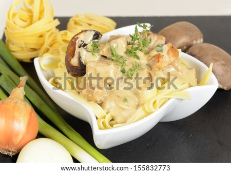 Dinner with tagliatelle and grilled mushrooms with chicken in delicious cream sauce. Image taken closeup on black background. - stock photo