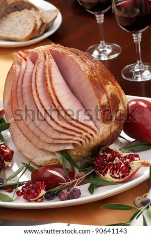 Dinning table set with glazed whole baked sliced ham, garnished with pomegranate, olives, and red pears. - stock photo