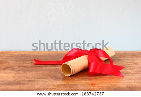 diploma scroll and red ribbon over wooden shelf - stock photo