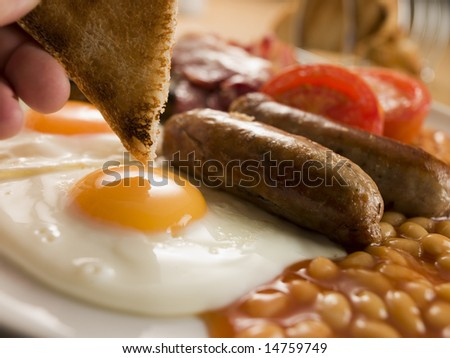 Dipping Toast into a Fried Egg on a Full English Breakfast - stock photo