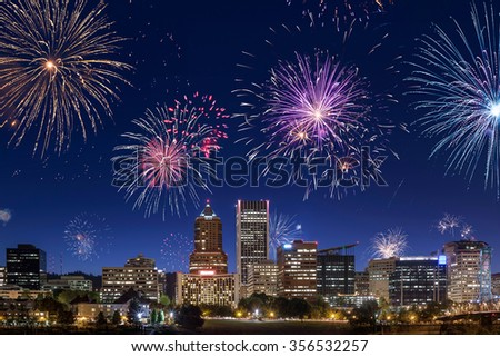 Direct view on Portland's downtown buildings and skyscrapers during night with fireworks on the sky - stock photo