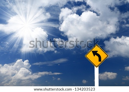 Direction sign- left turn sign pointing to rays of light on blue sky background - stock photo