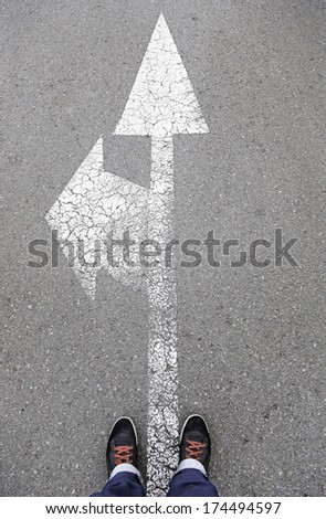 Directional arrow on the asphalt with a few feet, detail of a direction sign painted on the asphalt road safety - stock photo