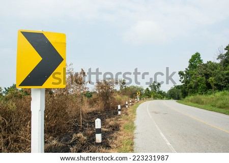 Directional arrow road signs pointing to the right as the road is right curve - stock photo