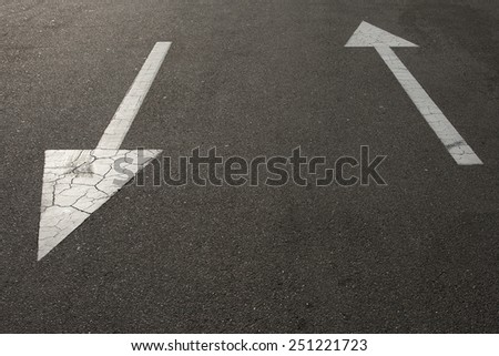 directional arrow signs on the asphalt road - stock photo