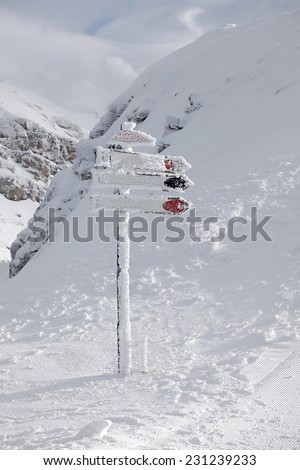 Directional sign post frozen in winter - stock photo