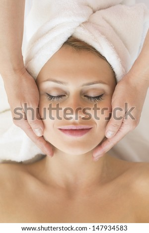 Directly above shot of beautiful young woman receiving facial massage in beauty spa - stock photo