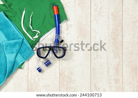 Directly above shot of swimming trunks; towel and snorkeling mask on floorboard - stock photo