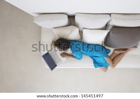 Directly above shot of woman using laptop on couch in living room - stock photo