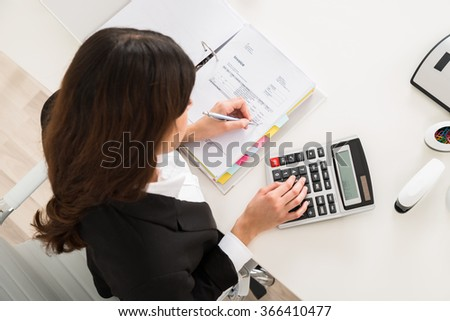 Directly above shot of young businesswoman doing financial calculation at desk in office - stock photo