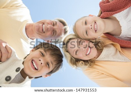 Directly below portrait of cheerful parents and children against clear blue sky - stock photo