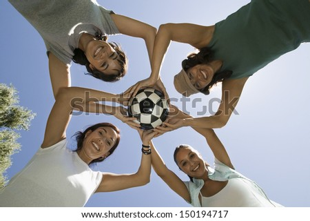 Directly below shot of female friends holding soccer ball against blue sky - stock photo