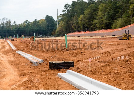 Dirt graded for roads in a residential construction site with new concrete curbs - stock photo