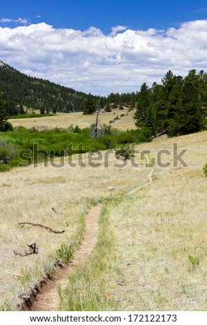 Dirt hiking trail climbs through the Colorado Rocky Mountains - stock photo