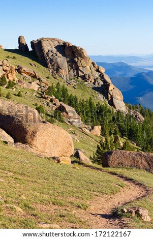 Dirt hiking trail winds through the Colorado Rocky Mountains on a clear blue sky day - stock photo
