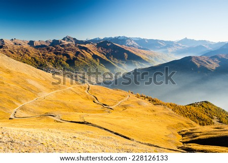 Dirt mountain road crossing alpine slopes and colorful meadows in autumn season at sunset. Wide angle view of misty valley and mountain range in the background. - stock photo