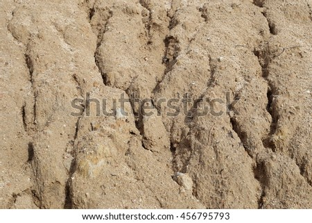 Dirt pile in vacant lot eroding and washing by rain water. - stock photo