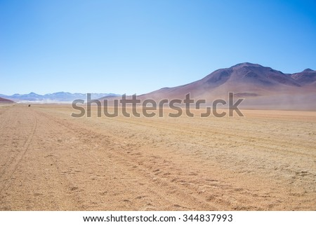 Dirt road at high altitude with sandy desert and barren volcano range on the Andean highlands. Road trip to the famous Uyuni Salt Flat, among the most important travel destination in Bolivia. - stock photo