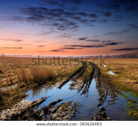dirt road in spring steppe after rain against sunset - stock photo