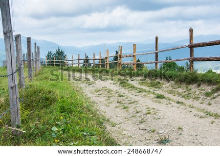 Dirt road in the mountains surrounded with wooden fence - stock photo