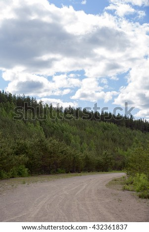 Dirt road in to the forest. Dramatic and cloudy sky. - stock photo