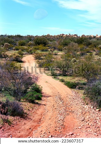 Dirt road leading off into the desert mountains moon in background - stock photo