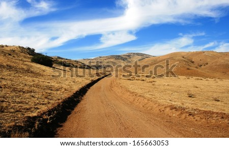 Dirt road leading through the high desert in the Antelope Valley, California - stock photo