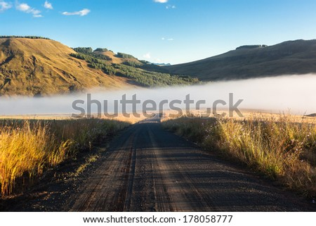 Dirt Road Mist Mountains Mountain wilderness Dirt Road with mist rising from rivers nearby - stock photo