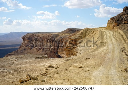 Dirt road on the edge of crater Ramon in Negev desert. Israel                                - stock photo