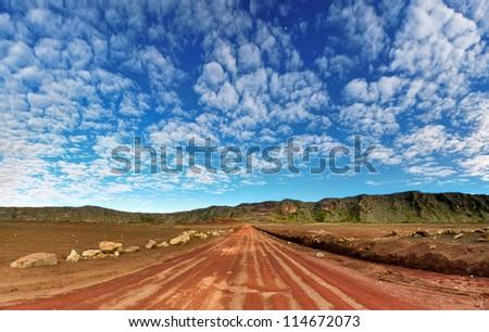 Dirt road on volcanic landscape of Plaine des Sables, Reunion Island National Park. - stock photo