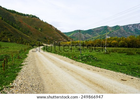Dirt road passing among the forested hills - stock photo