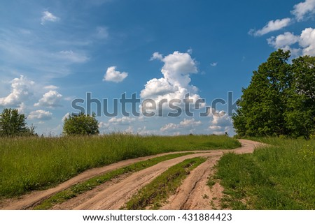 Dirt road to the green hill - stock photo