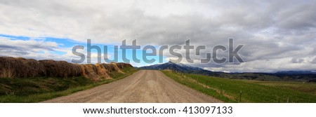 Dirt road with farmland and Rocky Mountains in background. - stock photo
