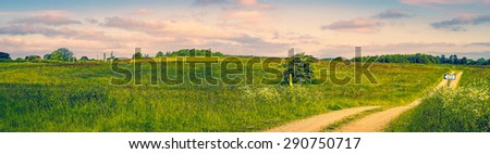 Dirt track on a countryside landscape with green fields - stock photo