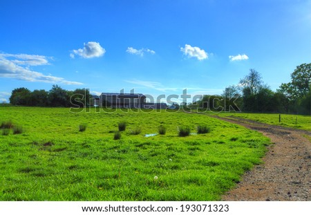 Dirt Track Through Field Leading up to Farm on Sunny Afternoon (HDR) - stock photo