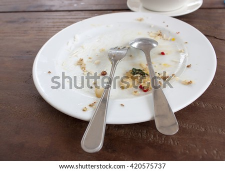 dirty and empty dishes on wood table - stock photo