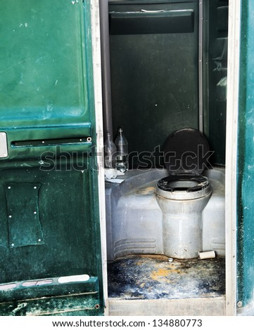Dirty and neglected chemical toilet booth positioned in a construction site. - stock photo