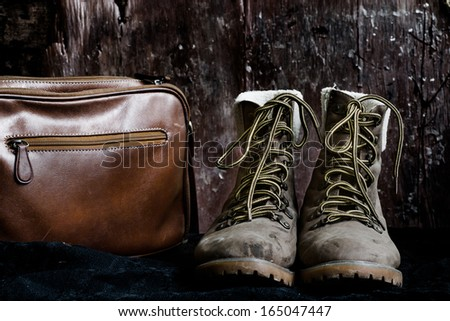 Dirty boots and brown bag, still life - stock photo