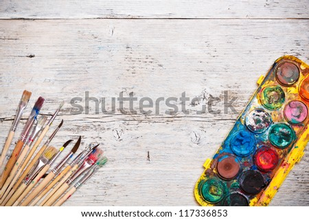 Dirty brushes with paints on wooden background - stock photo